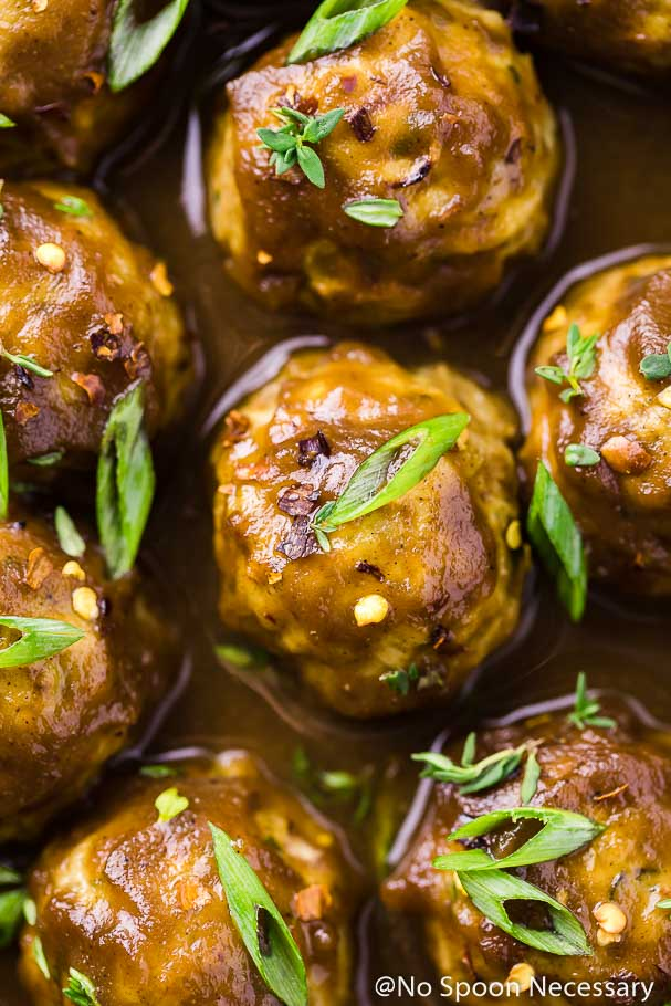 Overhead up-close shot of Baked Spiced Hard Apple Cider Glazed Meatballs garnished with sliced green onions, thyme and crushed red pepper flakes