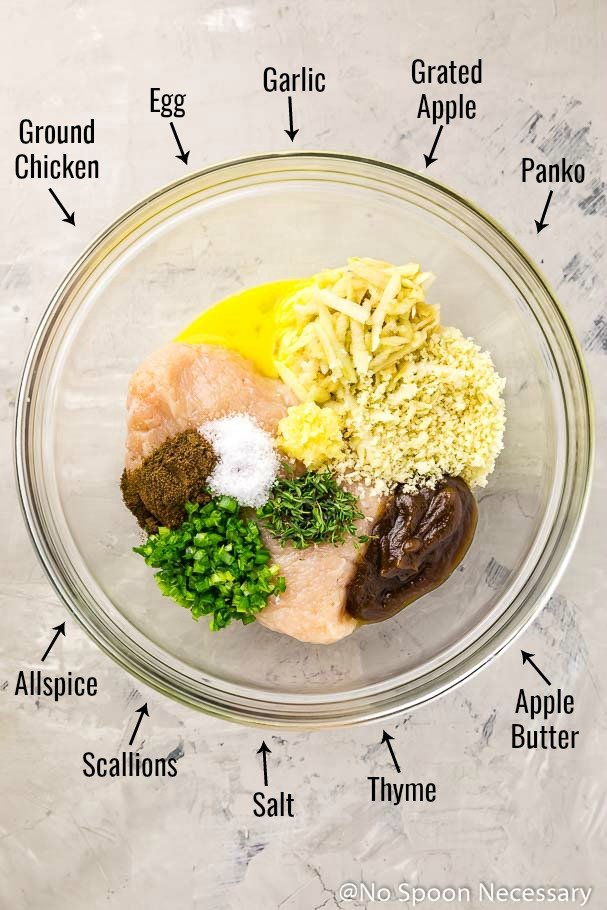 Overhead shot of the ingredients to make Baked Chicken Apple Meatballs in a glass bowl before mixing, with the ingredient name and an arrow pointing to each individual ingredient - photo of step 2 of the recipe.