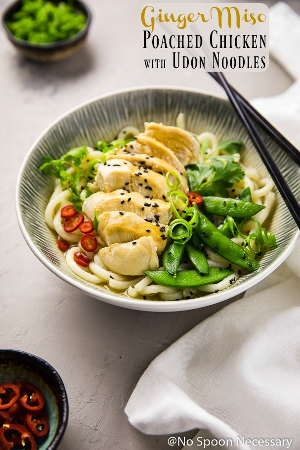 Angled shot of Ginger Miso Poached Chicken with Sugar Snap Peas and Udon Noodles in a white and blue bowl with chopsticks resting on the side of the bowl; a white linen, ramekin of scallions and ramekin of red chilies surrounding the bowl