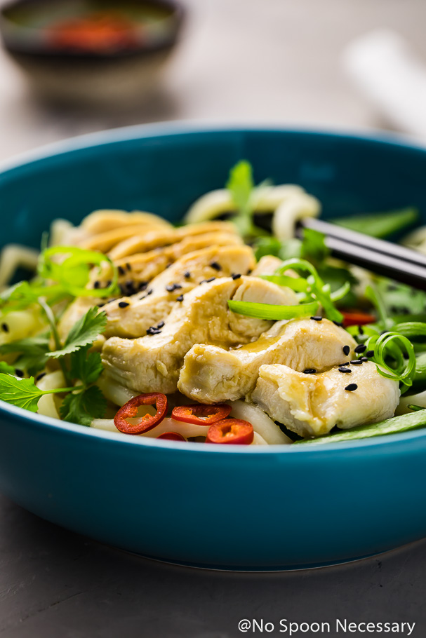 Straight on, up-close shot of Ginger Miso Poached Chicken on bed of udon noodles with fresh cilantro, red chilies and sugar snap peas; a pair of black chopsticks and ramekin of red chilies blurred in the background