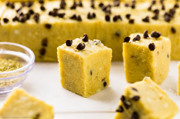 Straight on photo of a square piece of pumpkin fudge surrounded by more pieces of fudge.