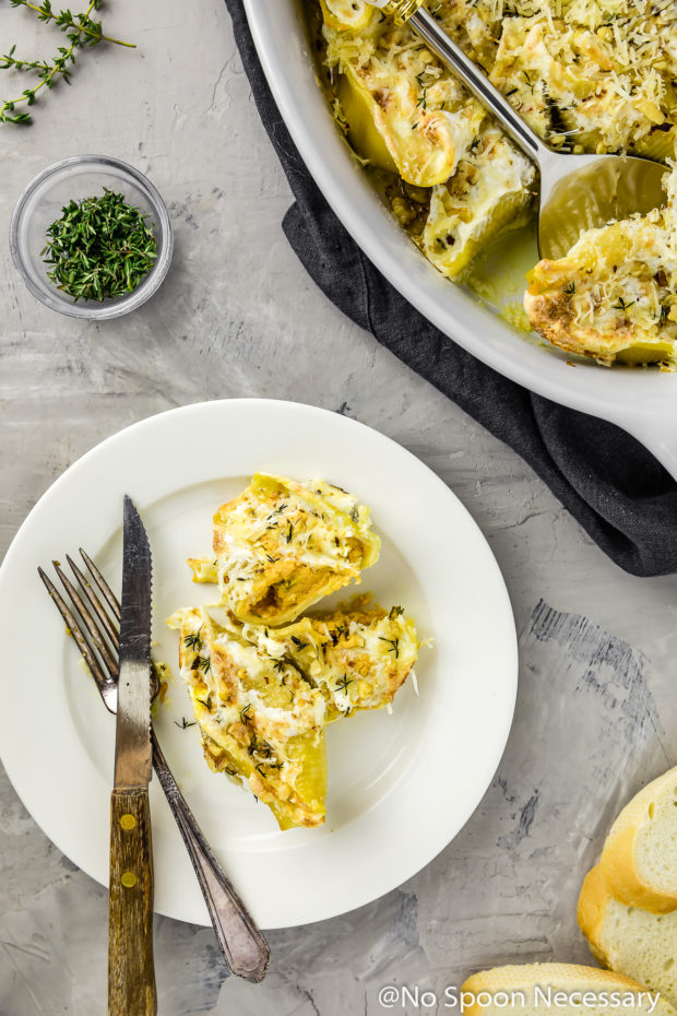 Overhead shot of a couple Baked Pumpkin Stuffed Shells topped with cheese on a small white plate with a knife and fork; with the baking dish of shells, slices of a baguette and fresh thyme surrounding the plate.