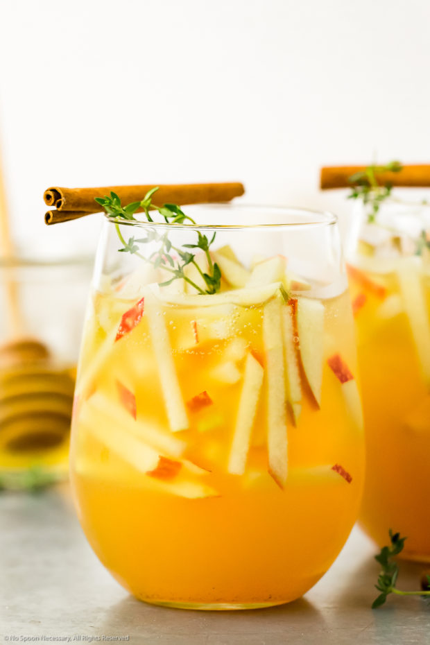 Straight on photo of a cocktail glass filled with an Apple and Gin Cocktail and garnished with matchstick cut apples, fresh thyme sprigs and cinnamon sticks.