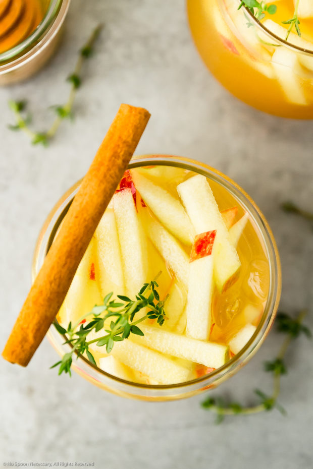 Overhead photo of an Apple Cocktail garnished with fresh slices of apples, thyme sprigs and a cinnamon stick.