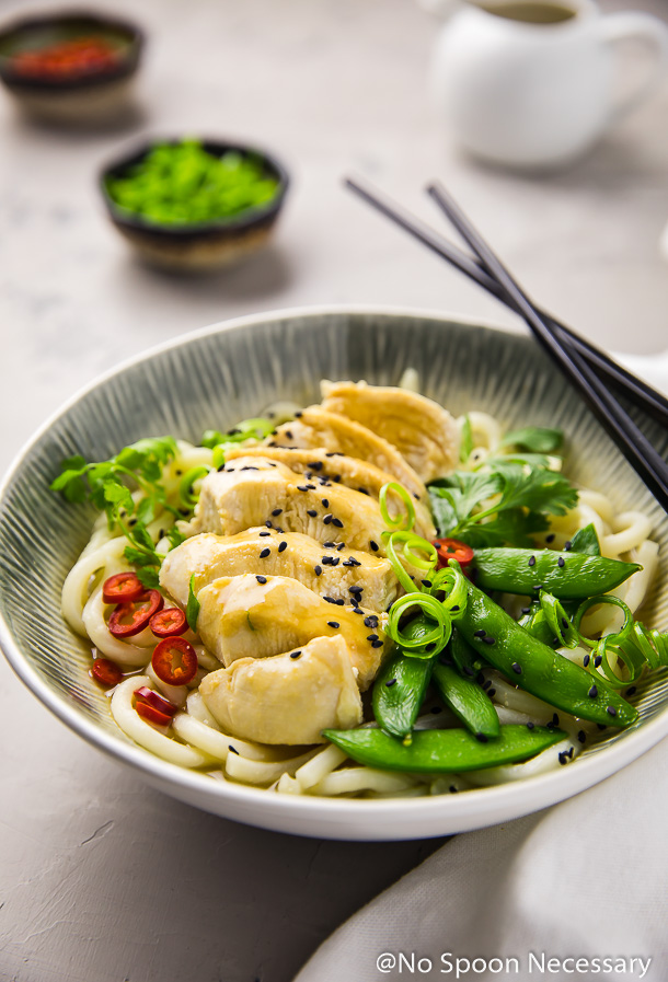 Angled shot of Ginger Miso Chicken with Sugar Snap Peas and Udon Noodles in a white and blue bowl with chopsticks resting on the side of the bowl; a white linen, small white tea pitcher, ramekin of scallions and ramekin of red chilies blurred in the background