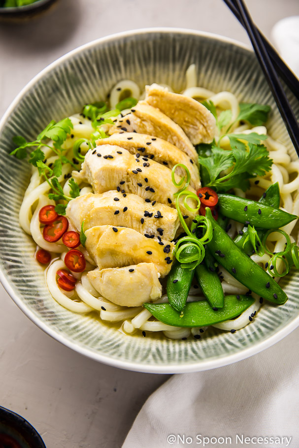 Angled, up close shot of a blue and white bowl filled with Ginger Miso Poached Chicken with Sugar Snap Peas and Udon Noodles with chopsticks resting on the side of the bowl