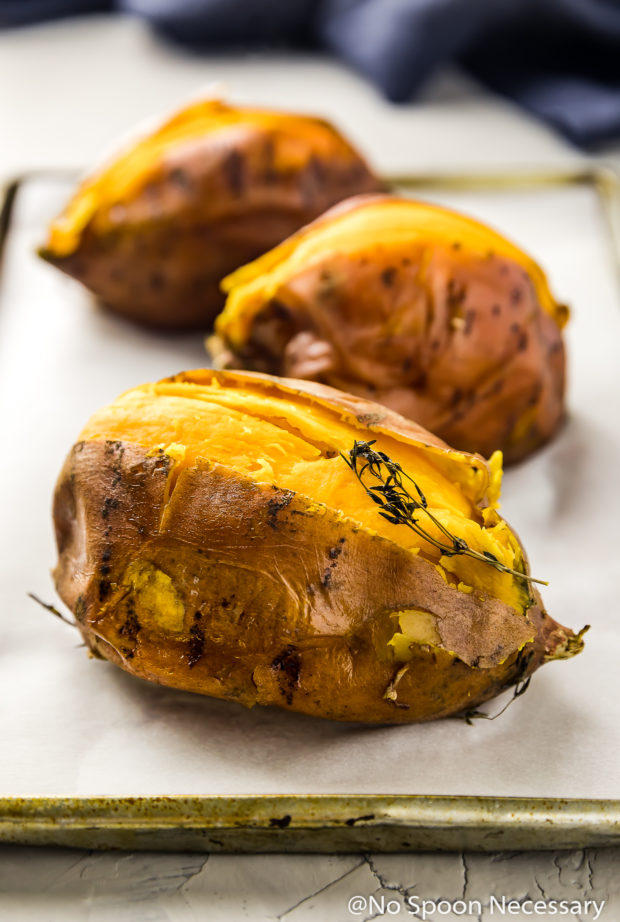 Angled shot of 3 cut open roasted sweet potatoes on a parchment paper lined small sheet pan with a blue linen in the background - photo of step 2 of the recipe.