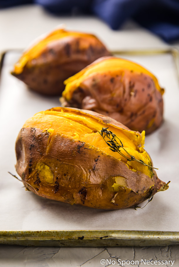 Angled shot of 3 cut open roasted sweet potatoes on a parchment paper lined small sheet pan with a blue linen in the background