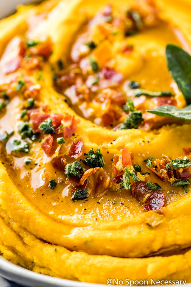 Angled, extremely up-close shot of whipped sweet potatoes topped with crispy, crumbled pancetta, crispy sage leaves and brown butter.