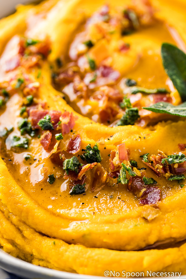 Angled, extremely up-close shot of whipped sweet potatoes topped with crispy, crumbled pancetta, crispy sage leaves and brown butter