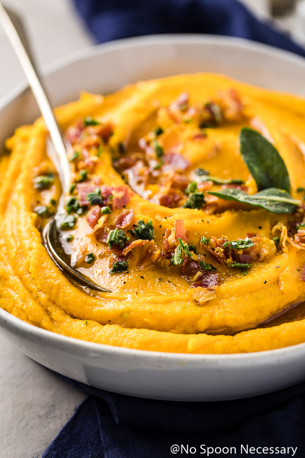 Angled shot of a neutral colored bowl containing whipped sweet potatoes topped with crispy, crumbled pancetta, crispy sage leaves and brown butter with a serving spoon inserted into the potatoes and a blue linen underneath the bowl