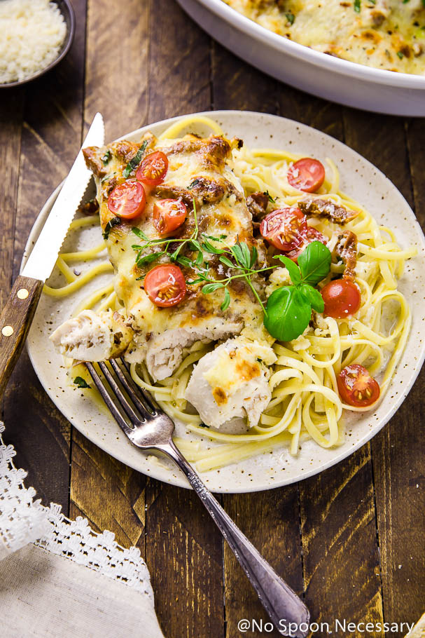 45 degree angle shot of a cut into Easy Cheesy Baked Sundried Tomato chicken breast on a plate with fettuccine, fresh cherry tomatoes, basil, knife and fork.