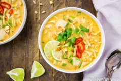 Overhead shot of Slow Cooker Thai Style Chicken Noodle Soup in a white bowl garnished with cilantro, lime wedges and sliced red chilies on a wood table with crushed peanuts, lime wedges. spoons, and a pale purple linen surrounding the bowl
