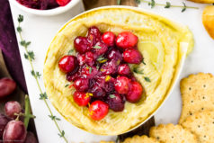 Overhead, landscape photo of Baked Camembert Cheese topped with burst Cranberries; with crackers and red grapes next to the cheese.
