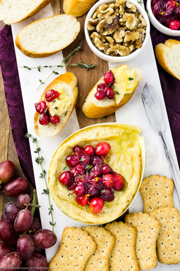 Overhead photo of a white cheese board featuring warm Camembert cheese topped with fresh cranberry sauce, slices of baguettes, a bowl of walnuts, crackers and red grapes, with a dark maroon napkin tucked under the cheese board.