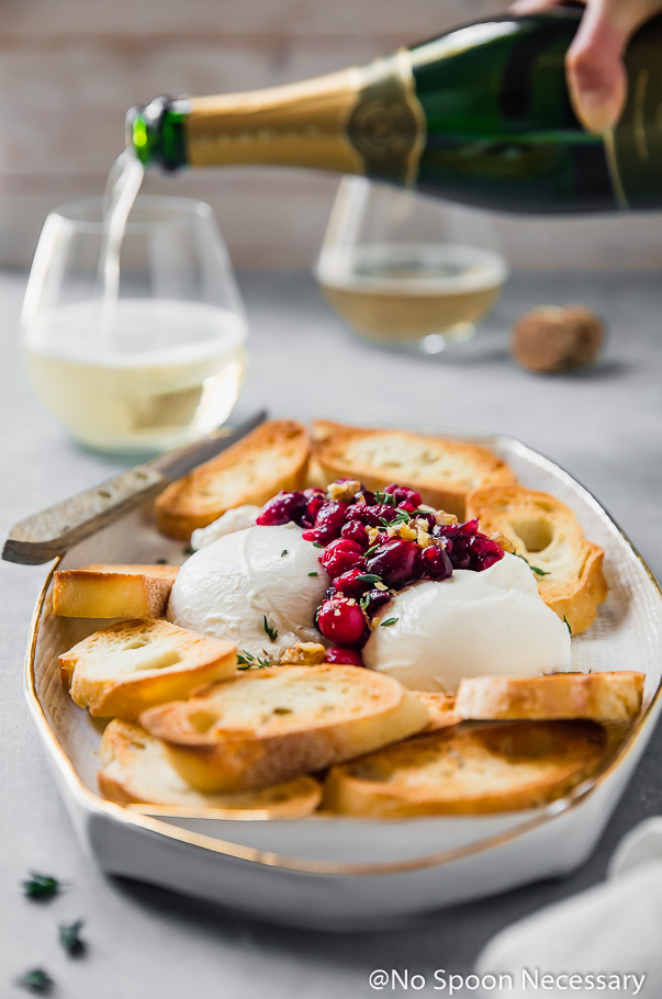 Angled shot of a white platter containing toasted slices of baguette and burrata topped with cranberry pomegranate relish, hazelnuts and fresh thyme with a small wooden handled knife resting on the tray; blurred in the background is a hand pouring champagne into wine glasses