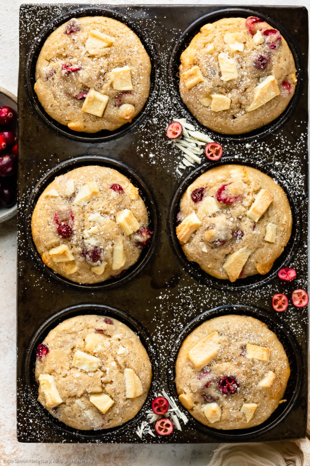 Overhead photo of White Chocolate and Cranberry Muffins dusted with powdered sugar in a muffin pan with a ramekin of fresh cranberries next to the pan.