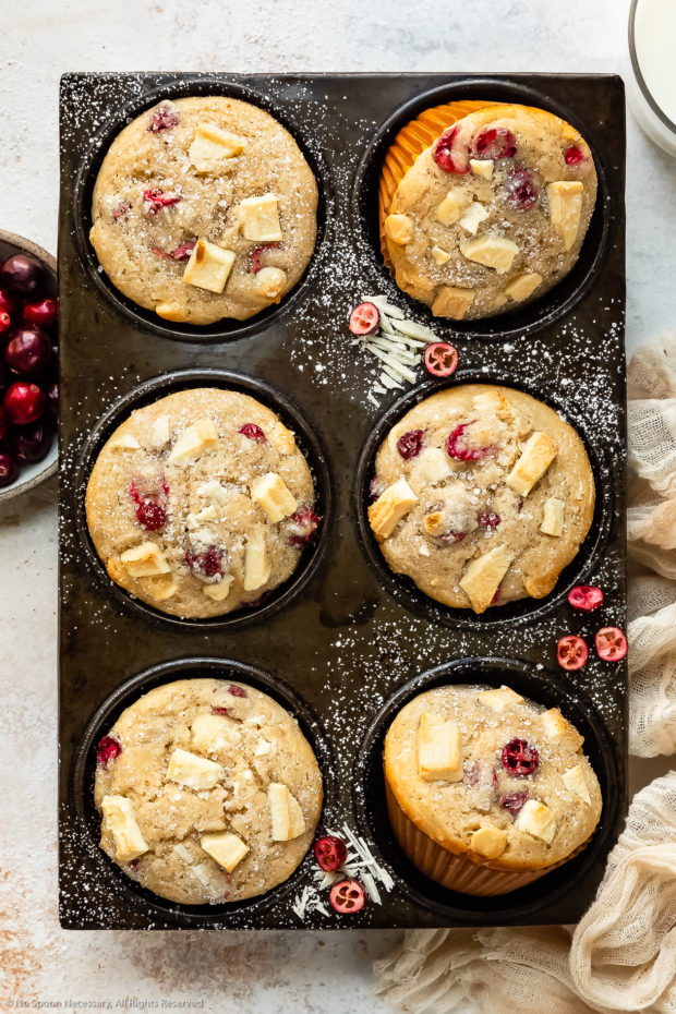 Overhead photo of Chocolate Cranberry Muffins dusted with powdered sugar in a muffin pan with a ramekin of fresh cranberries, glass of milk and pale tan napkin next to the pan.
