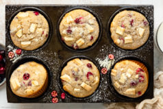 Overhead landscape photo of Chocolate Cranberry Muffins dusted with powdered sugar in a muffin pan with a ramekin of fresh cranberries, glass of milk and pale tan napkin next to the pan.