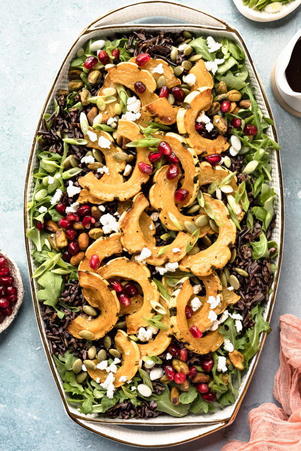 Overhead photo of Wild Rice Salad topped with delicata squash, pomegranate arils and sliced scallions on a white platter with ramekins of pomegranate arils, sliced scallions and a small container of honey balsamic vinaigrette arranged around the salad.