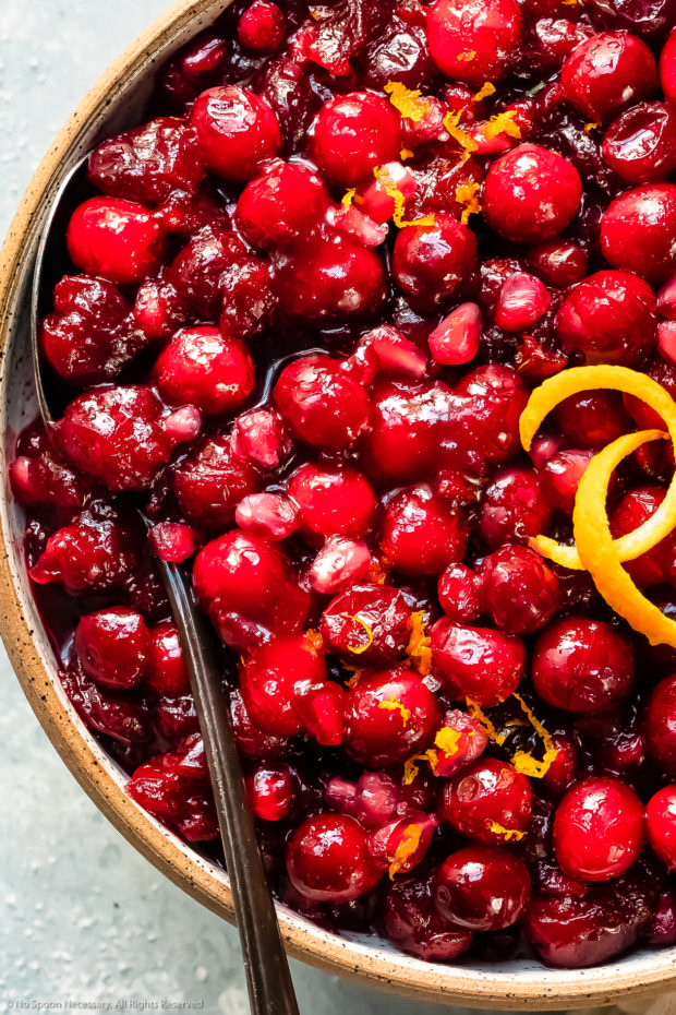 Overhead, close-up photo of Orange Cranberry Relish garnished with fresh orange zest in a white serving bowl.