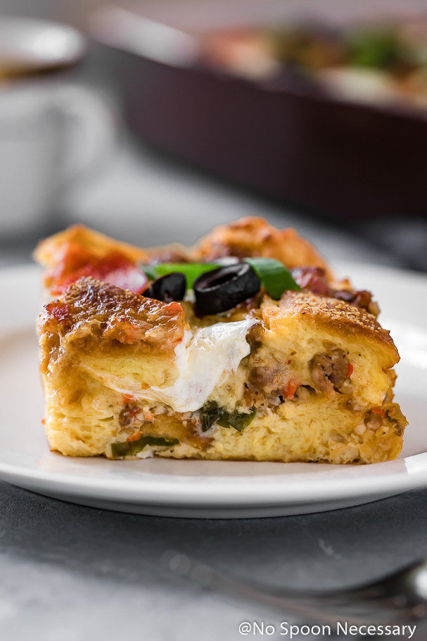 Straight on, up-close shot of the side of a slice of Supreme Strata with Burrata garnished with olives and scallions with a cup of coffee and a baking dish of the strata blurred in the background