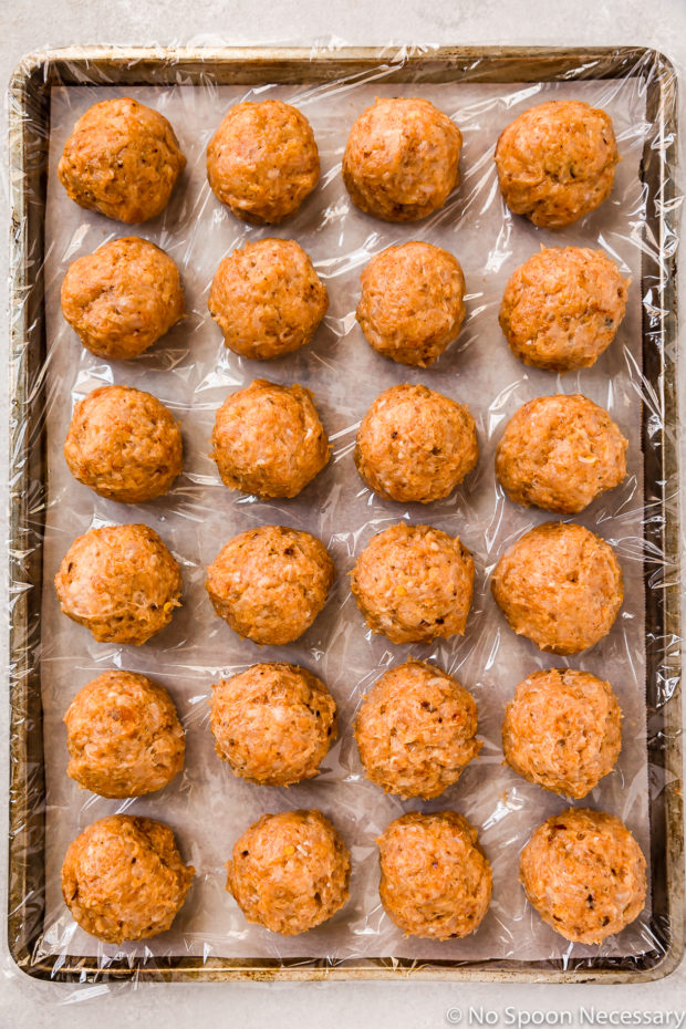 Overhead shot of prepared, unbaked spicy chicken meatballs on a plastic wrap lined baking sheet.