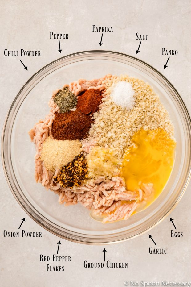 Overhead shot of a large glass bowl containing the ingredients to make spicy baked chicken meatballs with the ingredient name and an arrow pointing to each individual ingredient.