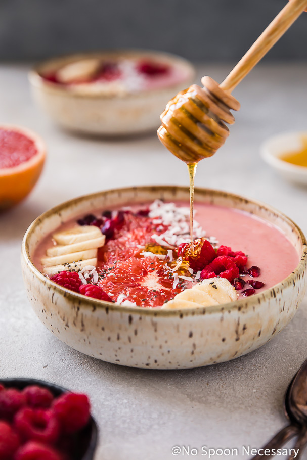 45 degree angle shot of honey being drizzled with a honey stick onto a Berry Citrus Smoothie Bowl topped with slices of bananas, grapefruit, whole raspberries, pomegranate arils and shredded coconut. There are fresh raspberries and two spoons blurred in the forefront and a half a grapefruit and another smoothie bowl blurred in the background.