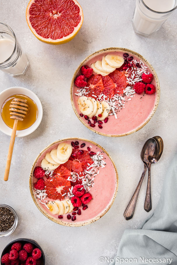 Overhead shot of two Berry Citrus Smoothie Bowls topped with slices of bananas, grapefruit, whole raspberries, pomegranate arils and shredded coconut. The bowls are surrounded by glasses of milk, a grapefruit half, 2 spoons, pale blue linen and ramekins of honey, chia seeds and raspberries.