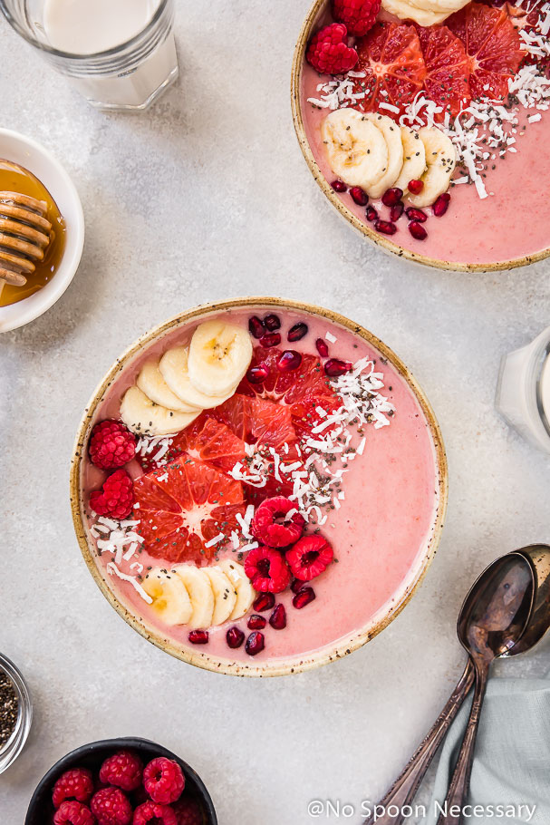 Overhead shot of a Berry Citrus Smoothie Bowl topped with slices of bananas, grapefruit, whole raspberries, pomegranate arils and shredded coconut. The bowl is surrounded by another smoothie bowl, glasses of milk, 2 spoons, pale blue linen and ramekins of honey and raspberries.