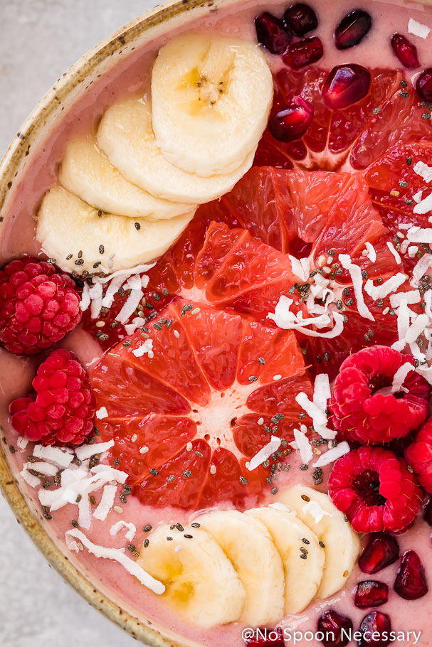 Overhead, extreme up-close shot of a Berry Citrus Smoothie Bowl topped with slices of bananas, grapefruit, whole raspberries, pomegranate arils, chia seeds and shredded coconut.