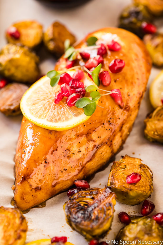 Overhead, up-close shot of a Honey Balsamic Pomegranate Chicken Breast with Brussels Sprouts garnished with lemon slices, pomegranate arils and micro greens.