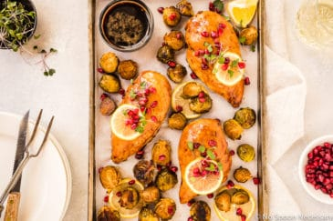 Overhead shot of a Sheet Pan containing Honey Balsamic Pomegranate Chicken & Brussels Sprouts garnished with lemon slices, pomegranate arils and micro greens; with a stack of plates, knife, meat fork, glass of wine, and small bowls of pomegranate arils and micro greens surrounding the pan.