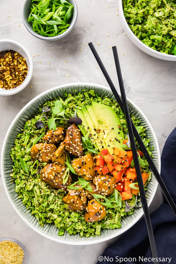 Overhead shot of a bowl filled with broccoli rice topped with Slow Cooker Honey Sesame Chicken, garnished with sesame seeds, sliced scallions, sliced avocados and diced red pepper. With a pair of black chop sticks laying on the side of the bowl and a blue linen, bowl of broccoli rice and ramekins of scallions, red pepper flakes and sesame seeds surrounding the bowl.
