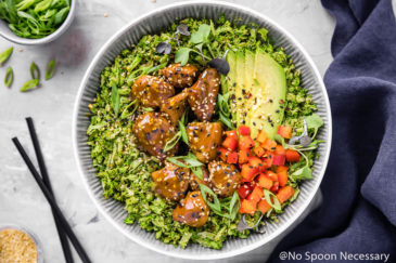 Overhead shot of a bowl filled with broccoli rice topped with Slow Cooker Honey Sesame Chicken, garnished with sesame seeds, sliced scallions, sliced avocados and diced red pepper. With a pair of black chop sticks, dark blue linen, and ramekins of sesame seeds and sliced scallions surrounding the bowl.