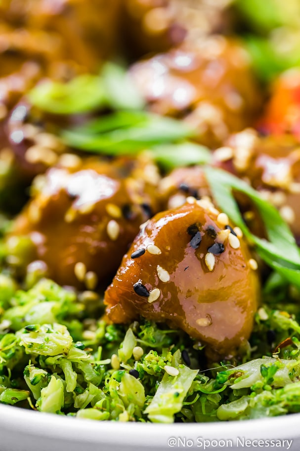 Angled, up-close shot of a single piece of Slow Cooker Honey Sesame Chicken sitting on a bed of broccoli rice with the rest of the chicken pieces blurred in the background.