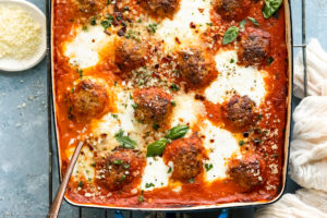 Overhead photo of a large baking dish filled with baked spicy chicken meatballs topped with cheese and basil with a large serving spoon inserted into the dish.