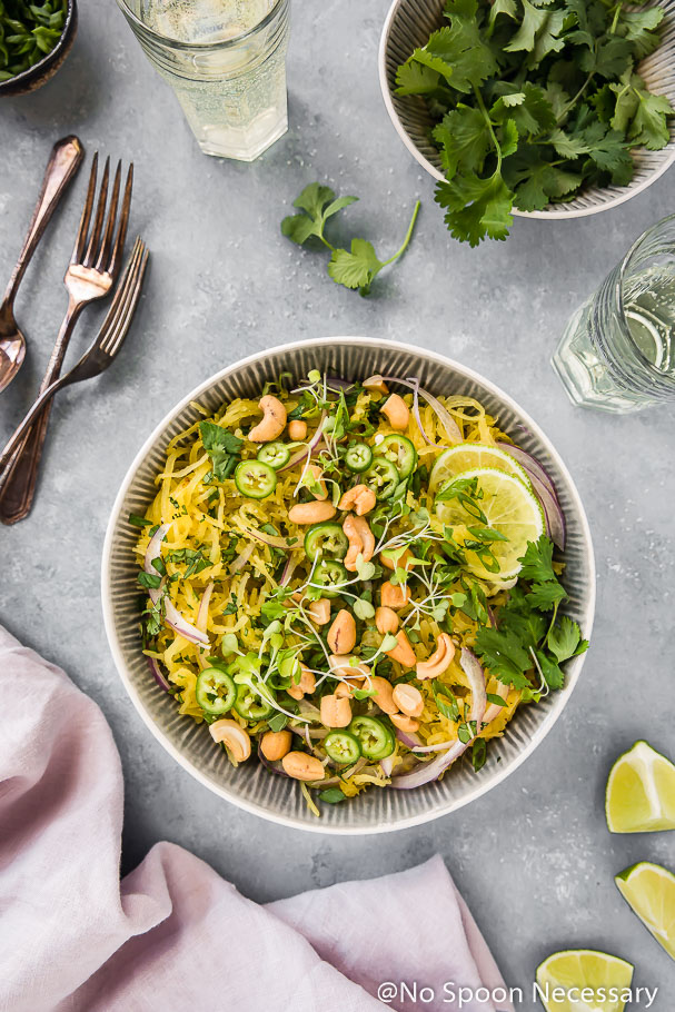 Overhead shot of a bowl of Spicy Thai Spaghetti Squash garnished with slices of red onion, jalapenos, crushed cashews, cilantro and lime slices; with a pale purple linen, forks, wine glasses, small bowl of cilantro and lime wedges surrounding the bowl.