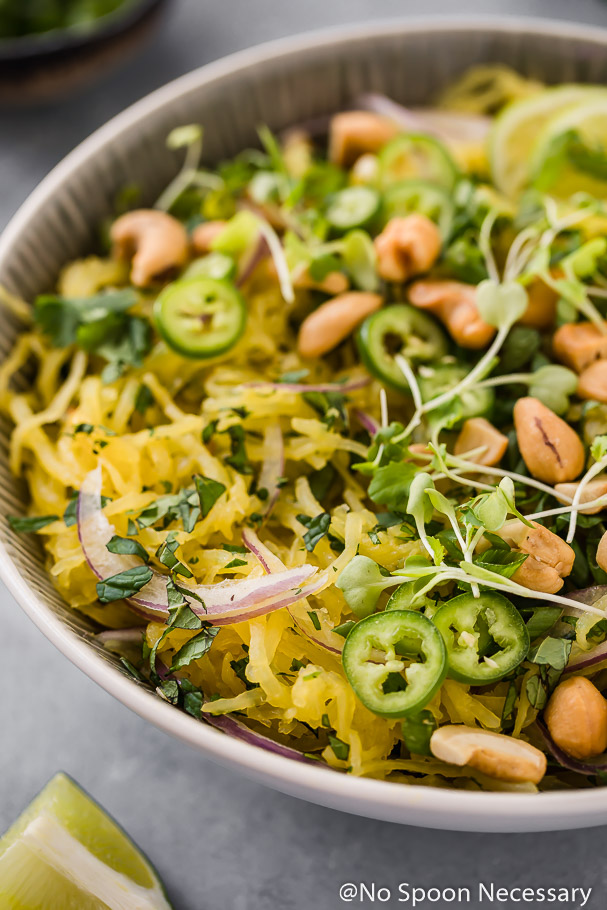 45 degree angle shot of a bowl of Spicy Thai Spaghetti Squash Salad garnished with slices of red onion, jalapenos, crushed cashews, cilantro and micro greens.