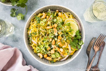 Overhead, landscape shot of a bowl of healthy Spicy Thai Spaghetti Squash Salad garnished with slices of red onion, jalapenos, crushed cashews, cilantro and lime slices; with a pale purple linen, forks, wine glasses, small bowl of cilantro and lime wedges surrounding the bowl.
