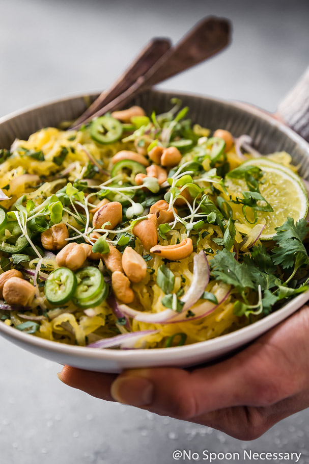 45 degree angle shot of two hands holding a bowl of Spicy Thai Spaghetti Squash garnished with slices of red onion, jalapenos, crushed cashews, cilantro and lime slices; with a fork and spoon tucked into the back of the bowl.