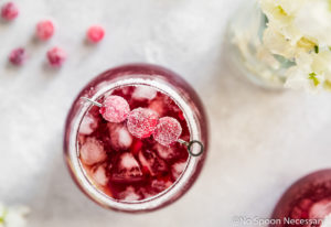 Overhead shot of a cocktail glass filled with Cranberry Pomegranate Margarita with a salt & sugar rim and garnished with sugared cranberries; with a small vase of white flowers, sugared cranberries and an additional cocktail surrounding the glass.