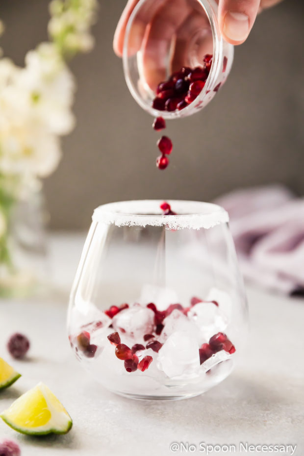 Straight on shot of a hand holding a small glass ramekin of pomegranate arils pouring the arils into an ice filled cocktail glass; with a small vase of white flowers and a purple linen blurred in the background. (Photo of the first part of step 4 of the recipe)