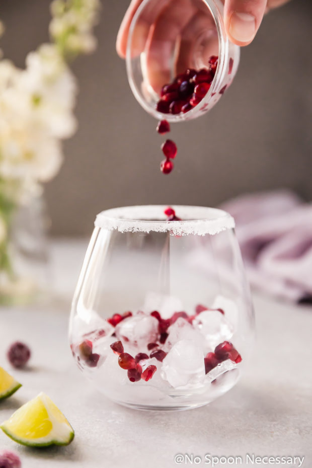 Straight on shot of a hand holding a small glass ramekin of pomegranate arils pouring the arils into an ice filled cocktail glass; with a small vase of white flowers and a purple linen blurred in the background.