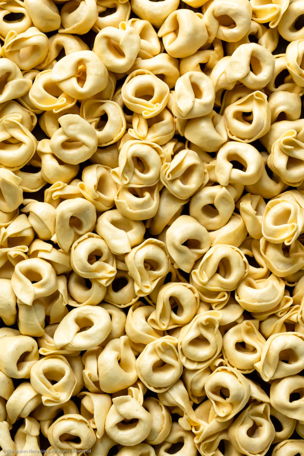 Overhead, close-up photo of a pile of dry tortellini - photo of the main ingredient in the soup recipe.