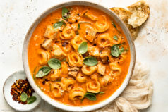 Overhead landscape photo of creamy chicken tortellini soup with tomatoes and spinach in a white serving bowl with a ramekin of red pepper flakes, crusty bread and a pale beige napkin next to the bowl.