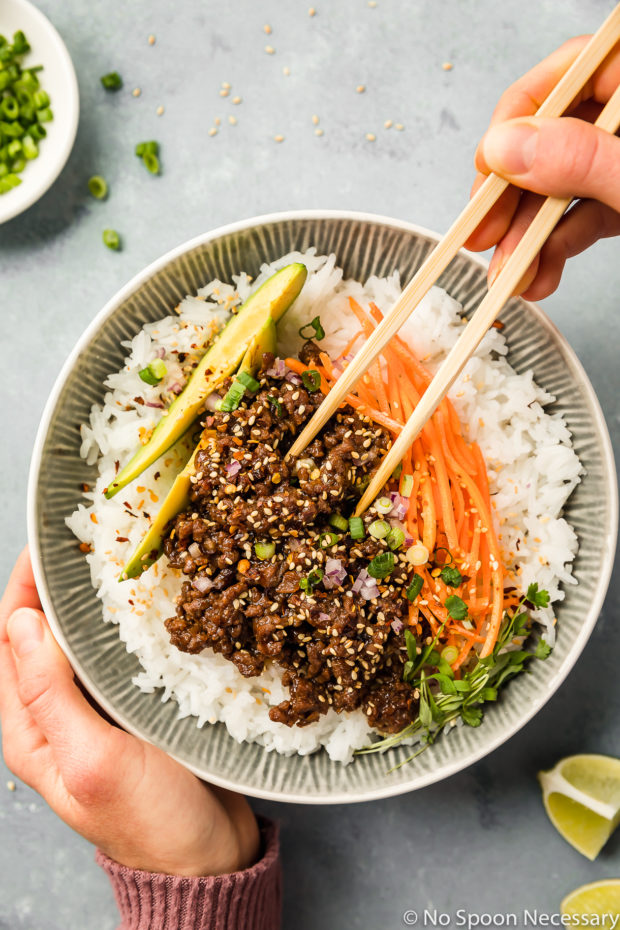 Overhead shot of a hand holding chop sticks eating a Stir-Fry Honey Hoisin Beef Bowl garnished with sliced avocado, matchstick carrots and sliced scallions with the other hand resting on the side of the bowl and a ramekin of scallions and lime wedges tucked in the corners of the shot.