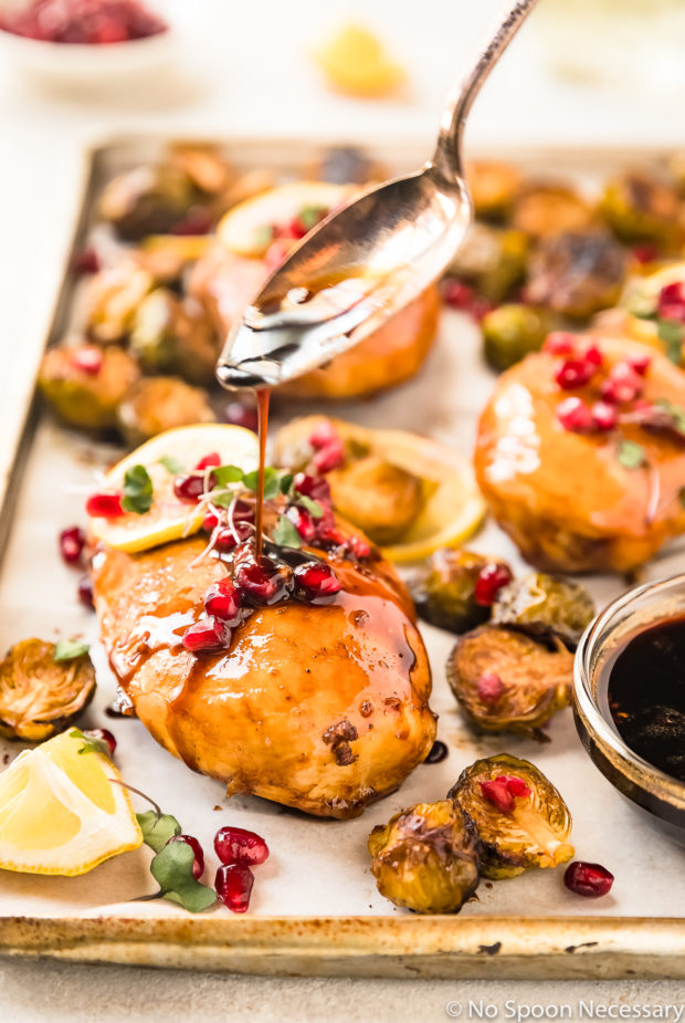 Straight on shot of a spoon drizzling Honey Balsamic sauce on to a Chicken Breast on a sheet pan with Brussels Sprouts, lemon slices, pomegranate arils and micro greens.