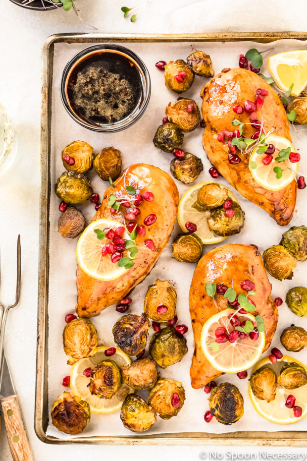 Overhead shot of part of a Sheet Pan containing Honey Balsamic Chicken & Brussels Sprouts garnished with lemon slices, pomegranate arils and micro greens with a ramekin of balsamic pomegranate sauce in the corner of the pan.